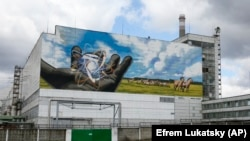 A huge mural decorates the wall at the entrance to the Chernobyl nuclear power plant, in Chernobyl, Ukraine, April 27, 2021.
