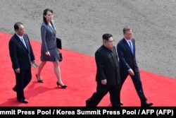North Korea's leader Kim Jong Un (2nd R) walks with South Korea's President Moon Jae-in (R), followed by Kim's sister and close adviser Kim Yo Jong (2nd L), down a red carpet to the official summit Peace House building for their meeting at Panmunjom on Ap