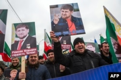 People shout slogans as they hold up images of the head of the Chechen republic Ramzan Kadyrov, during a rally in central Grozny, on January 22, 2016.