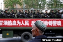 China-FILE PHOTO: A Uighur man looks on as a truck carrying paramilitary policemen travel along a street during an anti-terrorism oath-taking rally in Urumqi, Xinjiang Uighur Autonomous Region, China May 23, 2014. The Chinese characters on the banner read