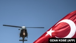 Turkish army helicopter flies behind a Turkish flag during a military parade marking the 93rd anniversary of Victory Day in Istanbul on August 30, 2015.