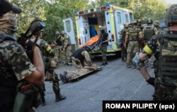 UKRAINE – Ukrainian soldiers rescue an injured comrade during fighting against militants, close to Ilovaysk, near Donetsk, August 10, 2014.