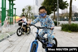 VIETNAM -- Children wearing a face mask as a preventive measure against the spread of COVID-19 novel coronavirus ride their bicycles in Hanoi on March 20, 2020.
