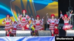 UKRAINE – People in traditional Ukrainian clothing performs on a stage during outdoor free ethno-rock festival Kozak Fest. Dnipropetrovsk region, June 2, 2018