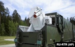 A Russian military truck with a laser weapon mounted on it is shown at an undisclosed location in Russia.
