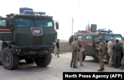 SYRIA -- Russian military police troops stand next to their armored vehicles in the northeastern Syrian city of Kobani, October 23, 2019