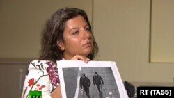 RT Editor-in-Chief Margarita Simonyan shows an image of two men during an interview with Anatoliy Chepiga (aka Ruslan Boshirov) and Dr. Alexander Mishkin (aka Alexander Petrov), suspected of poisoning former GRU officer Sergei Skripal and his daughter Yulia in Salisbury, England.