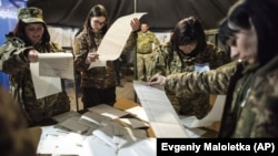 UKRAINE – Ukrainian government soldiers, members of the local election commission count ballots in a tent used as a polling station during the presidential elections in Mariinka, near a contact line not far from Donetsk, 31, 2019