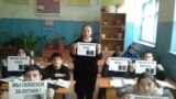 A teacher and her class in Dagestan take part in a pro-Putin action prior to 2018's Russian presidential election.