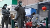 Statues with masks placed on them can be seen as a World Health Organization team visits Wuhan on February 9, 2021, to investigate origins of the COVID-19 pandemic. (Ng Han Guan/AP)