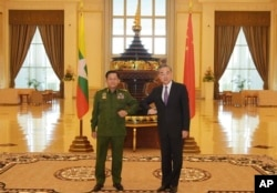 In this Jan. 12, 2021, file photo provided by Myanmar Military Information Team, Myanmar's Army Commander Senior Gen. Min Aung Hlaing, left, and Chinese Foreign Minister Wang Yi pose for a photo during their meeting in Naypyitaw, Myanmar.