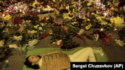 "UKRAINE – Ukrainian woman lies down in front of Dutch embassy holding a poster reading ""Putin is a killer,"" in Kyiv, July 17, 2014"