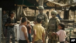 Russian soldiers escorting a group of journalists stand guard as children gather in Deir ez-Zor, September 15, 2017.