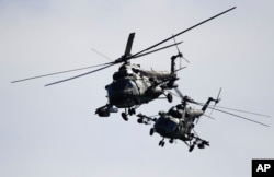Two Belorussian military helicopters fly during the Zapad military exercises with Russia near Volka, Belarus, September 19, 2017.
