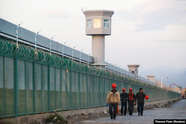 Workers walk by the perimeter fence of what is officially known as an education centre in Dabancheng, China on September 4, 2018