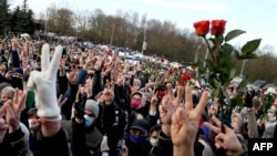 People flash the V-sign to pay tribute to late opposition protester Raman Bandarenka during his funeral ceremony in Minsk, Belarus on November 20, 2020.