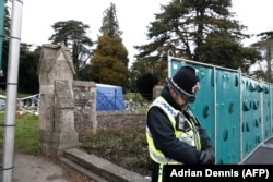 U.K. -- A policeman stands guard at temporary fencing at the London Road Cemetery where the wife and son of former Russian spy Sergei Skripal are buried, in Salisbur, March 14, 2018