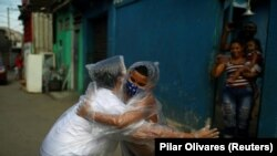 "Teacher Maura Silva, who created a ""hug kit"" using plastic covers, embraces her student Yuri Araujo Silva at Yuri's home, amid the coronavirus disease (COVID-19) outbreak. Source: Pilar Olivares (Reuters)"