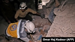 SYRIA -- Syrian rescuers, known as White Helmets, recover bodies in Zardana, in the mostly rebel-held northern Syrian Idlib province, following air strikes in the area, June 7, 2018