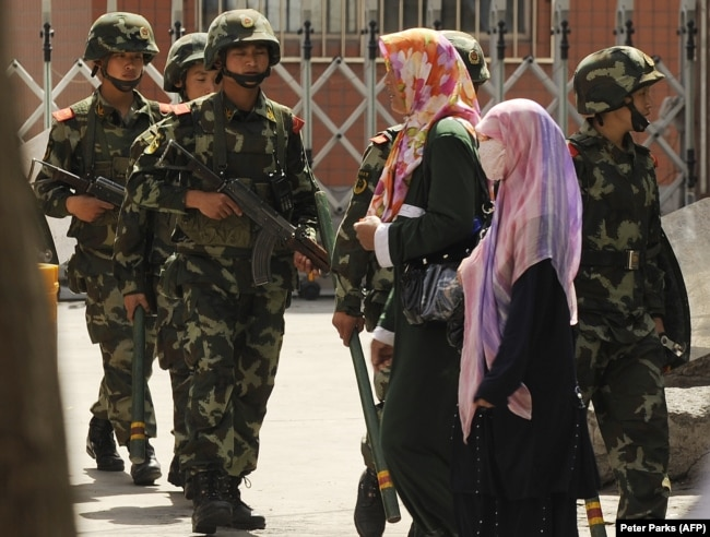 Muslim ethnic Uighur women pass a Chinese paramilatary police on patrol on a street in Urumqi, capital of China's Xinjiang region on July 3, 2010 ahead of the first anniversary of bloody violence that erupted in the region.