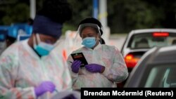 FILE PHOTO: Medical technicians work at a drive-through coronavirus disease (COVID-19) testing facility at the Regeneron Pharmaceuticals company's Westchester campus in Tarrytown, New York, U.S. September 17, 2020.