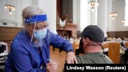 Ginger Ryder administers a vaccine to Dustin Armstrong as people are vaccinated against COVID-19, accompanied by live music from an organist, at a clinic held by 6M Geriatrics at Saint Mark's Episcopal Cathedral in Seattle, Washington, U.S. April 29, 2021.