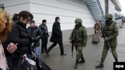 Ukraine -- Armed men patrol near a building of the airport in Simferopol, Crimea, February 28, 2014. Ukraine accused Russia of sending thousands of extra troops to Crimea.