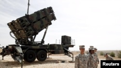 U.S. soldiers stand beside a U.S. Patriot missile system at a Turkish military base in Gaziantep, October 10, 2014.