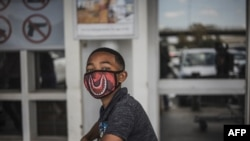 A boy wears a face mask as a preventive measure against the spred of the COVID-19 coronavirus as he queues outside Makro in Soweto, Johannesburg, on March 24, 2020.