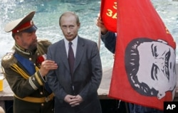 RUSSIA – A man dressed up to resemble Russian Czar Nicholas II, left, sets up a cardboard cutout of Russian President Vladimir Putin and another man, behind the flag, holds a red flag with former Soviet leader Josef Stalin. Moscow, July 13, 2012