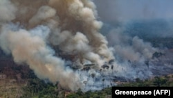 BRAZIL -- Smoke billows from forest fires in the municipality of Candeias do Jamari, close to Porto Velho in Rondonia State, in the Amazon basin, August 24, 2019.