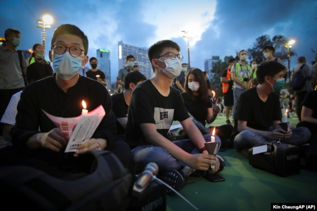 Hong Kong democracy activist Joshua Wong, center, holds a candle as he joins others for a vigil to remember the victims of the 1989 Tiananmen Square Massacre at Victoria Park in Causeway Bay, Hong Kong, Thursday, June 4,2020.