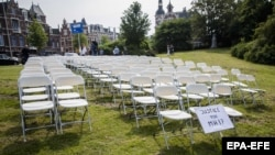 NETHERLANDS -- White chairs and a placard are set up by relatives of crash victims of flight MH17 as a silent protest in front of the Russian embassy in The Hague, May 8, 2018