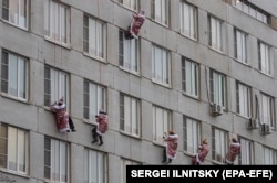 RUSSIA - Russian firemen and rescuers dressed in costumes of Father Frost (or Ded Moroz, or Santa Claus) descend along a wall from the roof of Morozovskaya Children's hospital.