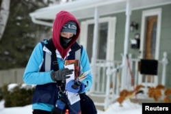Mail carrier Tiffany Sufficool delivers the mail during subzero (fahrenheit) temperatures in Fargo, North Dakota, U.S., January 31, 2019. REUTERS/Dan Koeck