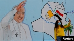 IRAQ - A woman takes selfies with a mural of Pope Francis on the wall of a church upon his upcoming visit to Iraq, in Baghdad, Iraq, February 22, 2021.