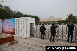 Foreign journalists take photos and video outside a location that that was identified in early 2020 as a re-education facility by an Australian think tank.
