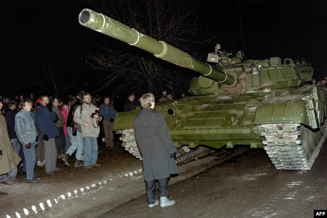 Lithuania -- Lithuanian demonstrator stands in front of a Soviet Red Army tank