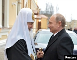 Russia's President Vladimir Putin (R) speaks with Patriarch of Moscow and All Russia Kirill during a visit to St. Sergius of Radonezh Cathedral in Tsarskoye Selo, outside St. Petersburg, December 8, 2014