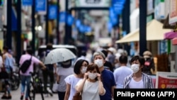 Japan -- People wearing face masks as a preventive measure against the COVID-19 coronavirus visit Togoshi Ginza shopping street in Tokyo on August 1, 2020. (Photo by Philip FONG / AFP)