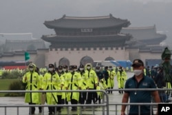 Police officers wearing face masks to help protect against the spread of the coronavirus patrol around the Gyeongbok Palace, one of South Korea's well-known landmarks, in Seoul, South Korea, Saturday, Aug. 15, 2020.
