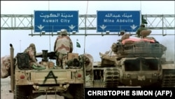 A US Hummvee jeep (l) and a Saudi tank pass under a highway sign directing them to Kuwait City 26 February 1991 during Desert Storm Allied forces offensive.