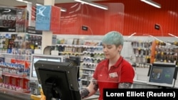 FILE PHOTO: A cashier works behind a protective plexiglass shield at a Coles supermarket following the easing of restrictions implemented to curb the spread of the coronavirus disease (COVID-19) in Sydney, Australia, June 17, 2020.