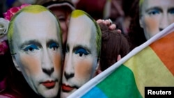 U.K. -- Protesters wearing masks of Russia's President Vladimir Putin pretend to kiss as they take part in a demonstration against the country's 'anti-gay' laws outside the Embassy of the Russian Federation in London, February 14, 2014.