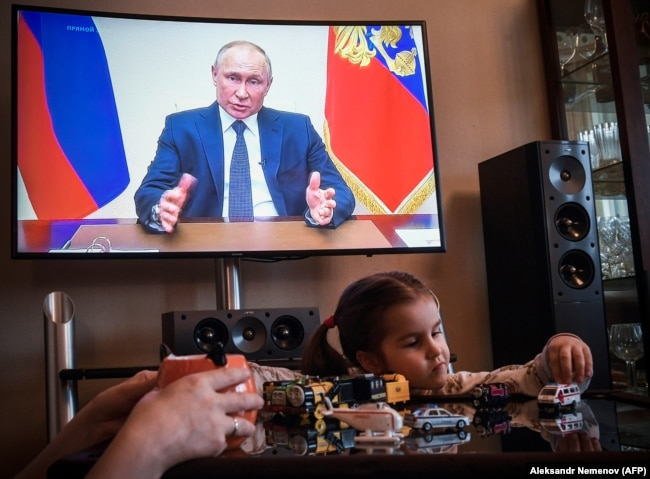 RUSSIA -- A woman watches a live broadcast of Russian President Vladimir Putin's address to the nation over the coronavirus outbreak, in her appartment in Moscow, April 2, 2020
