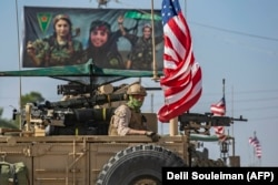 SYRIA -- A U.S. armored vehicle drives past a billboard for the Syrian Kurdish Women's Protection Units (YPJ), during a patrol of the Syrian northeastern town of Qahtaniyah at the border with Turkey, October 31, 2019