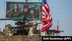 A U.S. armored vehicle drives past a billboard for the Syrian Kurdish Women's Protection Units (YPJ) during a patrol of the Syrian northeastern town of Qahtaniyah at the border with Turkey, October 31, 2019.