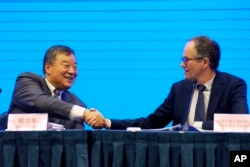 Peter Ben Embarek, of the World Health Organization team, right, shakes hands with his Chinese counterpart Liang Wannian after a WHO-China Joint Study Press Conference held at the end of the WHO mission in Wuhan, China, on Feb. 9, 2021.