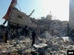 Syria -- People gather near a destroyed building said to be a Medecins Sans Frontieres (MSF) supported hospital in Marat al Numan, Idlib, February 15, 2016