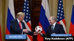FINLAND -- Russia's President Vladimir Putin (R) offers a ball of the 2018 football World Cup to US President Donald Trump during a joint press conference after a meeting at the Presidential Palace in Helsinki, on July 16, 2018.